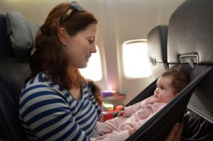 Mother carry her infant baby during flight.Concept photo of air travel with baby.